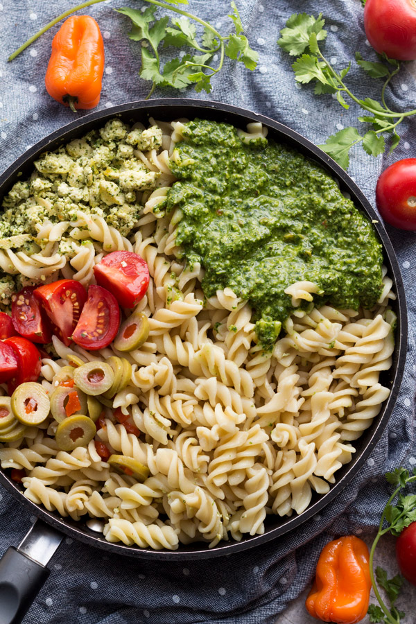This easy vegan cilantro pesto pasta is flavourful, spicy, filling and calls for just 10 ingredients and about 25 minutes. Perfect vegan lunch or dinner | ExSloth.com