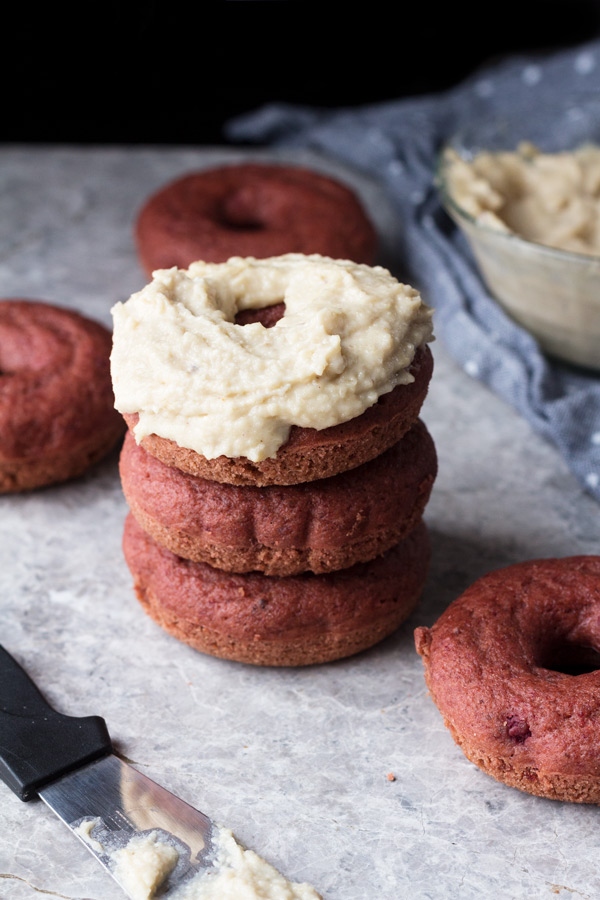 These vegan red velvet donuts are a delicious, healthy alternative to regular fried donuts and are great for Valentine's Day. The vegan cashew cream cheese frosting is also easy to make, creamy and perfectly sweet | ExSloth.com