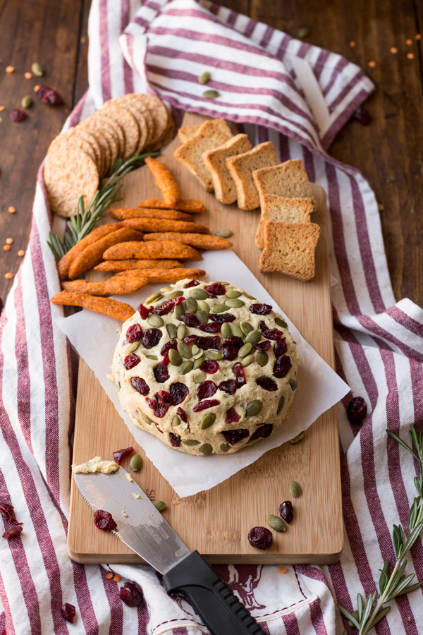 Vegan Lentil Cashew Cheese Ball - An easy vegan cheese recipe topped with cranberries and pumpkin seeds. Perfect for holiday or Christmas parties | ExSloth.com